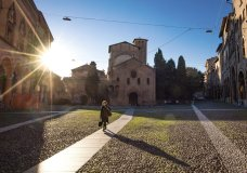 A woman walks past the Basilica of Santo Stefano, in Bologna, Italy, Wednesday, March 11, 2020. In Italy the government extended a coronavirus containment order previously limited to the country's north to the rest of the country beginning Tuesday, with soldiers and police enforcing bans. For most people, the new coronavirus causes only mild or moderate symptoms, such as fever and cough. For some, especially older adults and people with existing health problems, it can cause more severe illness, including pneumonia. (Massimo Paolone/LaPresse via AP)