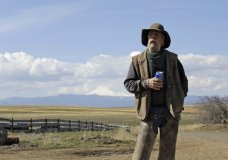 In this photo taken March 20, 2020, cattle rancher Mike Filbin stands on his property in Dufur, Ore., after herding some cows and talks about the impact the new coronavirus is having on his rural community. Tiny towns tucked into Oregon's windswept plains and cattle ranches miles from anywhere in South Dakota might not have had a single case of the new coronavirus yet, but their residents fear the spread of the disease to areas with scarce medical resources, the social isolation that comes when the only diner in town closes its doors and the economic free fall that's already hitting them hard. (AP Photo/Gillian Flaccus)