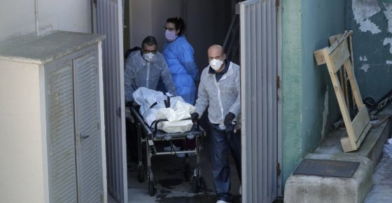 Funeral home workers carry a dead body from the Vitalia nursing homes in Leganes, Spain, Friday, April 3, 2020. The new coronavirus causes mild or moderate symptoms for most people, but for some, especially older adults and people with existing health problems, it can cause more severe illness or death. (AP Photo/Manu Fernandez)