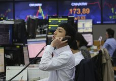 A currency trader talks on the phone at the foreign exchange dealing room of the KEB Hana Bank headquarters in Seoul, South Korea, Wednesday, April 22, 2020. Asian stock markets fell further Wednesday as oil prices recovered some of their record-setting losses amid anxiety about the coronavirus pandemic's mounting economic damage. (AP Photo/Ahn Young-joon)