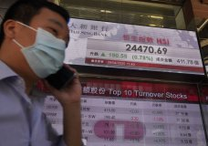 A man wearing face mask walks past a bank electronic board showing the Hong Kong share index at Hong Kong Stock Exchange Tuesday, April 28, 2020. Asian shares are mixed Tuesday as governments inch toward letting businesses reopen and central banks step in to provide cash to economies. (AP Photo/Vincent Yu)
