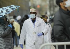 A medical worker walks past people lined up at Gotham Health East New York, a COVID-19 testing center Thursday, April 23, 2020, in the Brooklyn borough of New York. (AP Photo/Frank Franklin II)