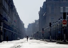 A woman stretches as she crosses the empty Rivoli street during a nationwide confinement to counter the Covid-19, in Paris, Sunday, April 5, 2020. The new coronavirus causes mild or moderate symptoms for most people, but for some, especially older adults and people with existing health problems, it can cause more severe illness or death. (AP Photo/Christophe Ena)