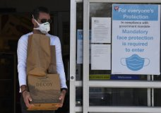 A shopper walks out of a store in Annapolis, Wednesday, April 15, 2020. Anne Arundel County is now requiring employees and shoppers to wear masks to help limit the spread of the coronavirus joining a few other counties in Maryland who are requiring the same. (AP Photo/Susan Walsh)