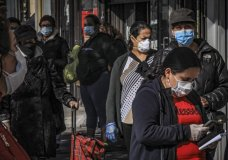 Women in Brooklyn's Sunset Park, a neighborhood with one of the city's largest Mexican and Hispanic community, wear masks to help stop the spread of coronavirus while waiting in line to enter a store, Tuesday May 5, 2020, in New York. A poll found that 61% of Hispanic Americans say they've experienced some kind of household income loss as a result of the COVID-19 outbreak. (AP Photo/Bebeto Matthews)