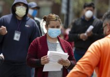 A woman waits to receive food at a distribution site during the coronavirus pandemic, Friday, May 8, 2020, in Chelsea, Mass. (AP Photo/Michael Dwyer)