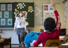 A teacher wearing protective face mask as she teaches close to pupils at a primary school in Morges, Switzerland, Monday, May 11, 2020. Swiss primary and secondary schools reopened with half of the students during the ongoing coronavirus Covid-19 pandemic. (Laurent Gillieron/Keystone via AP)