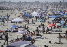 Visitors gather on the beach Sunday, May 24, 2020, in Newport Beach, Calif., during the coronavirus outbreak. (AP Photo/Marcio Jose Sanchez)