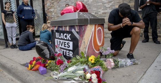 People gather and pray around a makeshift memorial, Tuesday, May 26, 2020, in Minneapolis, near the site where a black man, who was taken into police custody the day before, later died. The FBI and Minnesota agents are investigating the death of a black man in Minneapolis police custody after video from a bystander showed a white officer kneeling on his neck during his arrest as he pleaded that he couldn't breathe. (Elizabeth Flores/Star Tribune via AP)