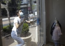 Dayanara Nieto cleans windows outside of Janie and Jack, a children's clothing store where she is a salesperson, at The Grove shopping center Wednesday, May 27, 2020, in Los Angeles. California moved to further relax its coronavirus restrictions and help the battered economy. Retail stores, including those at shopping malls, can open at 50% capacity. (AP Photo/Marcio Jose Sanchez)