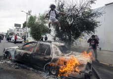 A person jumps on a burning police vehicle in Los Angeles, Saturday, May 30, 2020, during a protest over the death of George Floyd. Floyd died in Minneapolis police custody on Memorial Day. (AP Photo/Ringo H.W. Chiu)