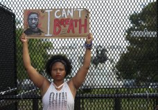 A demonstrator holds a sign as people protest Friday, June 5, 2020, near the White House in Washington, over the death of George Floyd, a black man who was in police custody in Minneapolis. Floyd died after being restrained by Minneapolis police officers. (AP Photo/Manuel Balce Ceneta)