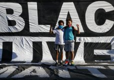 "Khai Rieara, 10, left, and his brother Keanu Rieara, 12, of Frederick, Md., stand on the Black Lives Matter banner that is draped on the fence surrounding Lafayette Park, for a photograph as they attend a protest Sunday, June 7, 2020, near the White House in Washington over the death of George Floyd, who died May 25 after being restrained by police in Minneapolis. ""Keanu has been talking about it a lot,"" said his mother, ""he feels it's inhuman what happened to George Floyd, that nobody helped him and that he didn't deserve that. He wants to know if that's going to happen to him."" (AP Photo/Jacquelyn Martin)"