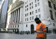 A man wearing a mask walks by the New York Stock Exchange, Tuesday, June 16, 2020. Stocks are rising sharply in early trading on Wall Street after retail sales in the U.S. soared by a record 17.7% from April to May, double what economists were expecting and a welcome sign that spending is partially rebounding after the devastating coronavirus shutdowns. (AP Photo/Mark Lennihan)