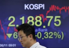 A currency trader walks by a screen showing the Korea Composite Stock Price Index (KOSPI) at the foreign exchange dealing room in Seoul, South Korea, Thursday, June 11, 2020. Asian shares were mostly lower Thursday, with Tokyo dropping more than 1% as the Japanese yen gained after the Federal Reserve said it would keep interest rates low through 2022. (AP Photo/Lee Jin-man)