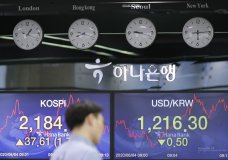 A currency trader walks by the screens showing the Korea Composite Stock Price Index (KOSPI), left, and the foreign exchange rate between U.S. dollar and South Korean won at the foreign exchange dealing room in Seoul, South Korea, Thursday, June 4, 2020. Asian stock markets are mixed after Wall Street rose on better U.S. jobs and manufacturing data than expected.(AP Photo/Lee Jin-man)