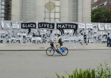 Pedestrians and a cyclist pass a mural in Union Square calling for justice over the death of George Floyd, and to highlight police brutality nationwide, Thursday, June 11, 2020, in New York. Floyd, a black man, died after he was restrained by Minneapolis police on May 25. (AP Photo/Frank Franklin II)