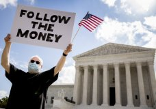 "Bill Christeson holds up a sign that reads ""Follow the Money"" outside the Supreme Court, Thursday, July 9, 2020, in Washington. The Supreme Court ruled Thursday that the Manhattan district attorney can obtain Trump tax returns while not allowing Congress to get Trump tax and financial records, for now, returning the case to lower courts. (AP Photo/Andrew Harnik)"
