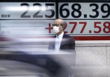 A man wearing a face mask to help curb the spread of the coronavirus stands near an electronic stock board showing Japan's Nikkei 225 index at a securities firm in Tokyo Monday, July 13, 2020. Asian shares rose Monday, cheered by recent upbeat projections on a global rebound tempered with worries about disappointment that could follow.(AP Photo/Eugene Hoshiko)