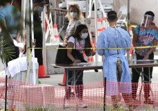 A health care worker signs people up for testing at a COVID-19 testing site at the Miami Beach Convention Center, during the coronavirus pandemic, Monday, July 13, 2020, in Miami Beach, Fla. (AP Photo/Lynne Sladky)