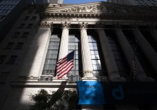 An American flag hangs at the New York Stock Exchange, Thursday, July 16, 2020. Stocks are opening broadly lower on Wall Street Thursday, extending weakness in overseas markets. (AP Photo/Mark Lennihan)