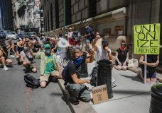 Protesters gather for a rally outside the Federal Reserve in the Financial District, Monday, July 20, 2020, in the Manhattan borough of New York. Thousands across the country planned to walked off the job to protest systemic racism and economic inequality that has worsened during the coronavirus pandemic. (AP Photo/John Minchillo)