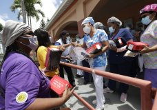 Union members hand out masks to prevent the spread of the new coronavirus and lunches to workers at the Franco Nursing & Rehabilitation Center, Monday, July 20, 2020, in Miami. Most facilities, experts and industry leaders told The Associated Press that a statewide mask mandate would help protect staff members, and consequently residents, from the virus. (AP Photo/Wilfredo Lee)