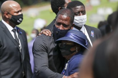 Family members embrace at the burial service for Rep. John Lewis at South-View Cemetery in Atlanta Thursday, July 30, 2020. (Alyssa Pointer/Atlanta Journal-Constitution via AP)