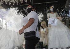A shopper passes a display window with mask covered mannequins at a dress store, Thursday, July 30, 2020, in McAllen, Texas. (AP Photo/Eric Gay)