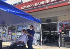A customer of Cosmo's barber shop receives a haircut in the parking lot in front of the shop on Wednesday, July 22, 2020, in Pleasanton, Calif. Throughout May and June, California reopened much of its economy, and people resumed shopping in stores and dining in restaurants. NBut infections began to surge and a new round of business restrictions were imposed, including a ban on indoor dining in restaurants and bars.(AP Photo/Ben Margot)