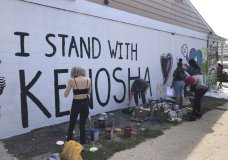 "Volunteers paint murals on boarded-up businesses in Kenosha, Wis., on Sunday, Aug. 30, 2020, at an ""Uptown Revival."" The event was meant to gather donations for Kenosha residents and help businesses hurt by violent protests that sparked fires across the city following the police shooting of Jacob Blake. (AP Photo/ Russell Contreras)"