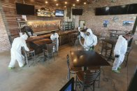 Workers from Servpro disinfect Mugshots restaurant in Tupelo, Mississippi, Friday, July 17, 2020, as the restaurant is preparing to open for business. (Thomas Wells/Northeast Mississippi Daily Journal via AP)