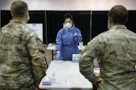 Diana Vega, a registered respiratory therapist, instructs Nevada National Guardsman on how to test people during the setup of a temporary coronavirus testing site Monday, Aug. 3, 2020, in Las Vegas. (AP Photo/John Locher)