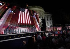 The Republican National Convention video is displayed on a screen as people watch from the South Lawn of the White House on the fourth day of the convention Thursday, Aug. 27, 2020, in Washington. (AP Photo/Alex Brandon)
