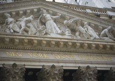 FILE - Marble sculptures occupy the pediment above the New York Stock Exchange signage, Tuesday Aug. 25, 2020, in New York. Stocks are pushing further into record heights on Wall Street Thursday, after the Federal Reserve made a major overhaul to its strategy, one that could keep interest rates lower for longer. (AP Photo/Bebeto Matthews)