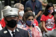 A woman wearing a flag mask joins others in prayer at the Tunnel to Towers ceremony (AP Photo/Mark Lennihan)
