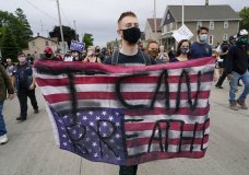 EDS NOTE: OBSCENITY - A protester holds a flag during a Black Lives Matter protest Tuesday, Sept. 1, 2020, in Kenosha, Wis. (AP Photo/Morry Gash)