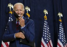 Democratic presidential candidate former Vice President Joe Biden smiles as he puts on his face mask after speaking to media in Wilmington, Del., Friday Sept. 4, 2020. (AP Photo/Carolyn Kaster)