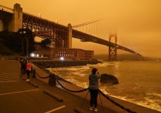 People stop at Fort Point to take morning pictures of the Golden Gate Bridge covered in smoke from wildfires Wednesday, Sept. 9, 2020, in San Francisco. (AP Photo/Eric Risberg)