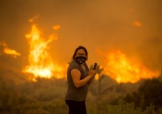 A woman watches as the Bobcat Fire burns in Juniper Hill, Calif., Friday, Sept. 18, 2020. (AP Photo/Ringo H.W. Chiu)