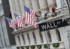 FILE - In this Jan. 3, 2020 file photo, the Wall St. street sign is framed by American flags flying outside the New York Stock Exchange in New York. U.S. stocks are swinging between losses and gains in Thursday, Sept. 24, trading, as volatility continues to be the dominant force in Wall Street's tumultuous September. (AP Photo/Mary Altaffer, File)