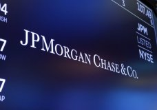 FILE - In this Aug. 16, 2019, file photo, the logo for JPMorgan Chase & Co. appears above a trading post on the floor of the New York Stock Exchange in New York. JPMorgan Chase admitted Tuesday, Sept. 29, 2020 to manipulating the markets for precious metals and U.S. Treasuries, agreeing to pay $920 million in fines and penalties for the illegal behavior. (AP Photo/Richard Drew, File)