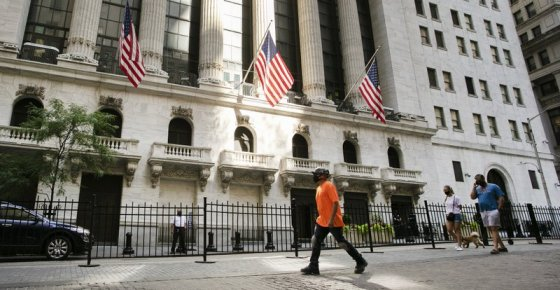 FILE- In this July 21, 2020 file photo, people walk by the New York Stock Exchange. Stocks are edging higher on Wall Street at the beginning of another busy week for corporate earnings news. The S&P 500 climbed 0.5% in the first few minutes of trading Monday, Oct. 19. (AP Photo/Mark Lennihan, File)