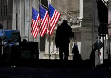 FILE - In this Oct. 14, 2020 file photo, pedestrians pass the New York Stock Exchange in New York. Stocks are opening higher on Wall Street Tuesday, Oct. 20 as traders look over several solid earnings reports from U.S. companies. (AP Photo/Frank Franklin II, File)
