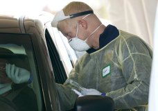 FILE - In this Oct. 28, 2020, file photo, a worker wearing gloves, a face shield, a mask, and other PPE administers a COVID-19 test at a King County coronavirus testing site in Auburn, Wash., south of Seattle. The latest surge in U.S. coronavirus cases appears to be larger and more widespread than the two previous ones, and it is all but certain to get worse. But experts say there are also reasons to think the nation is better able to deal with the virus than before, with the availability of better treatments, wider testing and perhaps greater political will. (AP Photo/Ted S. Warren, File)