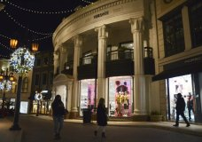 """A woman looks at the fashion in the holiday window display at the Louis Vuitton store on a mostly deserted Rodeo Drive, Monday, Nov. 30, 2020, in Beverly Hills, Calif. The three-week """"safer at home"""" order began on Monday. Indoor retail businesses, which make much of their profits during the Thanksgiving and Christmas holiday seasons, are allowed to remain open but with just 20% of capacity, including nail salons and other personal care services. (AP Photo/Pamela Hassell)"""
