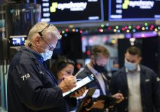 In this photo provided by the New York Stock Exchange, traders work on the floor, Monday, Dec. 7, 2020. U.S. stocks are taking a pause from their big recent rally, and most stocks on Wall Street are edging lower Monday following mixed and mostly muted movements for markets overseas. (Colin Ziemer/New York Stock Exchange via AP)