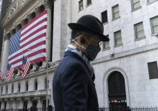 FILE - In this Nov. 16, 2020 file photo, a man wearing a mask passes the New York Stock Exchange, in New York. U.S. stocks are falling from their record highs Monday, Jan. 4, 2021, as trading gets underway in a year where the dominant expectation is for a powerful economic rebound to eventually sweep the world. (AP Photo/Mark Lennihan, File)