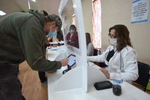 Poll worker Jennifer Jones, right, signs voter Taylor Ledford in at a polling place at Dawnville United Methodist Church in Dawnville, Ga., on Tuesday, Jan. 5, 2021. (Matt Hamilton/Chattanooga Times Free Press via AP)