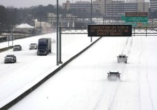 An electronic message board advises drivers of potential congestion on the intersecting interstate as they drive south on Interstate 55 in north Jackson, Miss., Monday, Feb. 15, 2021, as light snow mixed with sleet, and rain continue to cover much of the state. The National Weather Service forecasts temperatures barely hovering at 20 degrees Fahrenheit, and likely slipping into the single digits by Tuesday morning. A winter storm warning continues throughout the state. (AP Photo/Rogelio V. Solis)